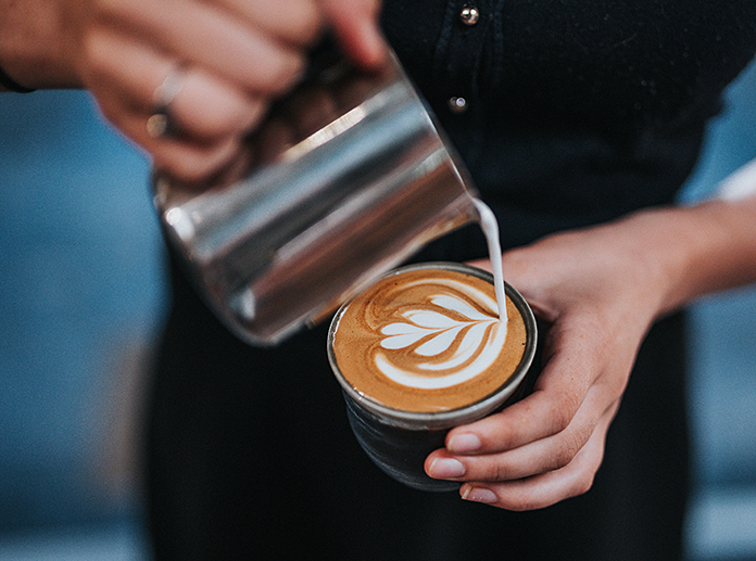 frau macht kaffee latte art